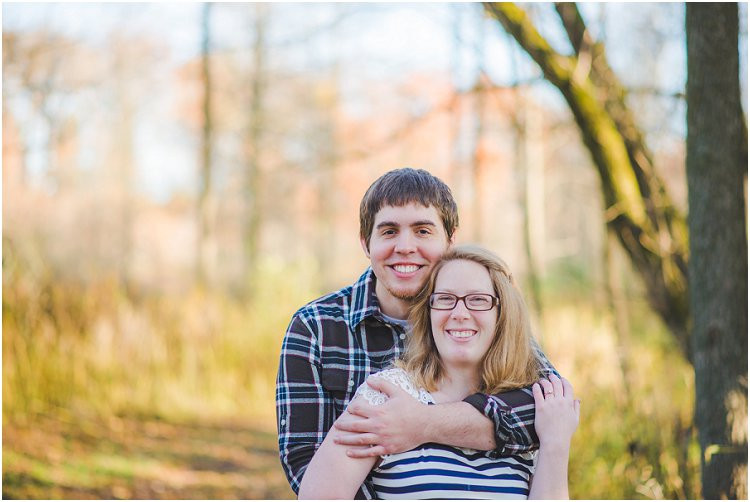 engaged-couple-smiling-at-camera-at-maywood-environmental-park-engagement-session-by-appleton-wedding-photography-kyra-rane-photography