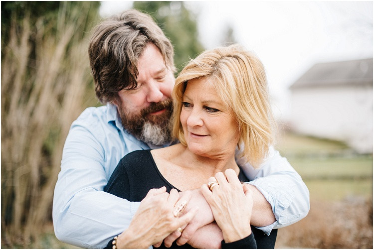 husband-wrapping-arms-around-wife-at-in-home-anniversary-session-by-appleton-wedding-photographer-kyra-rane-photography