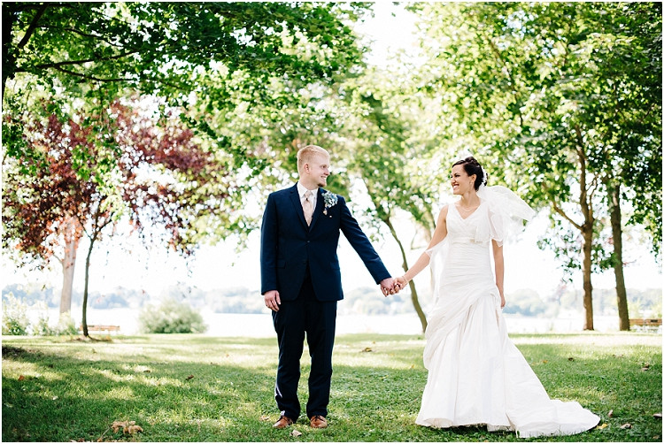bride-and-groom-smiling-and-holding-hands-at-de-pere-wedding-by-appleton-wedding-photographer-kyra-rane-photography