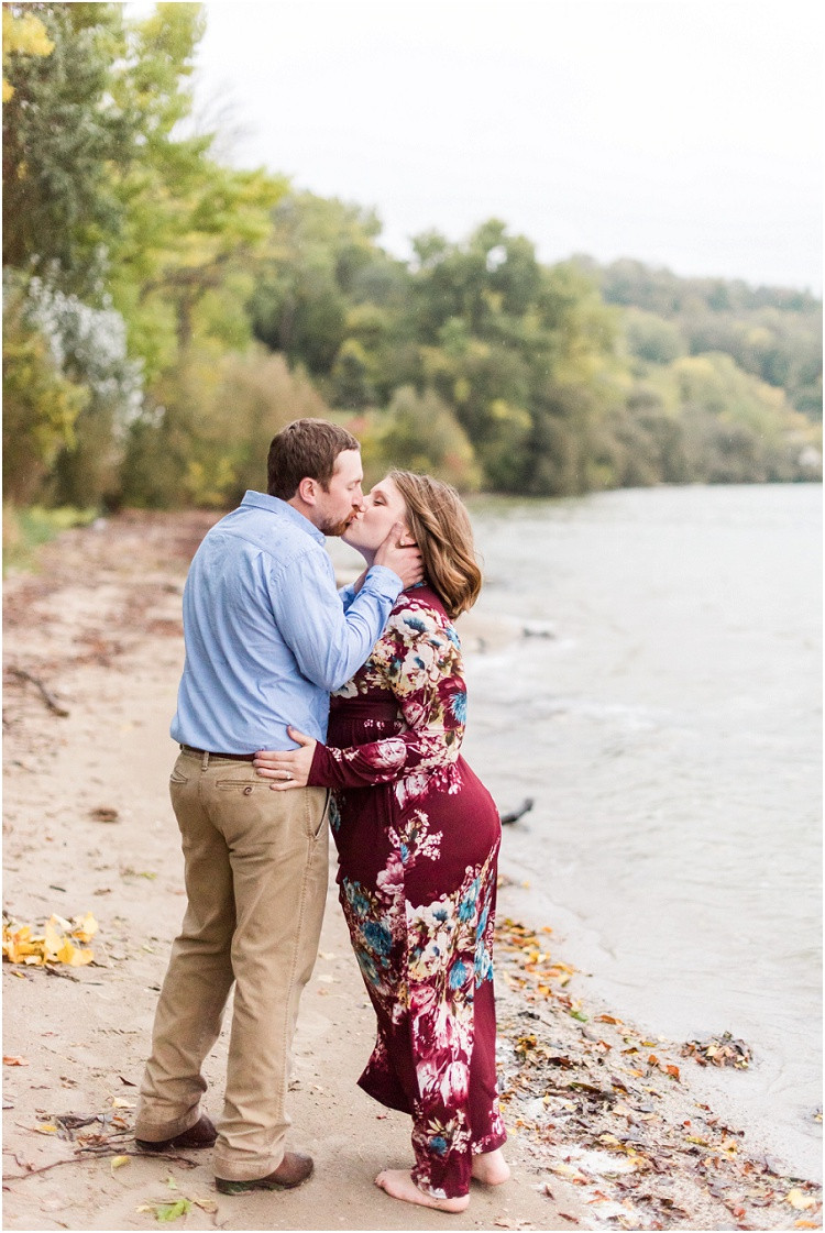 engaged-couple-kiss-by-lake-at-high-cliff-engagement-session-by-milwaukee-wedding-photographer-kyra-rane-photography