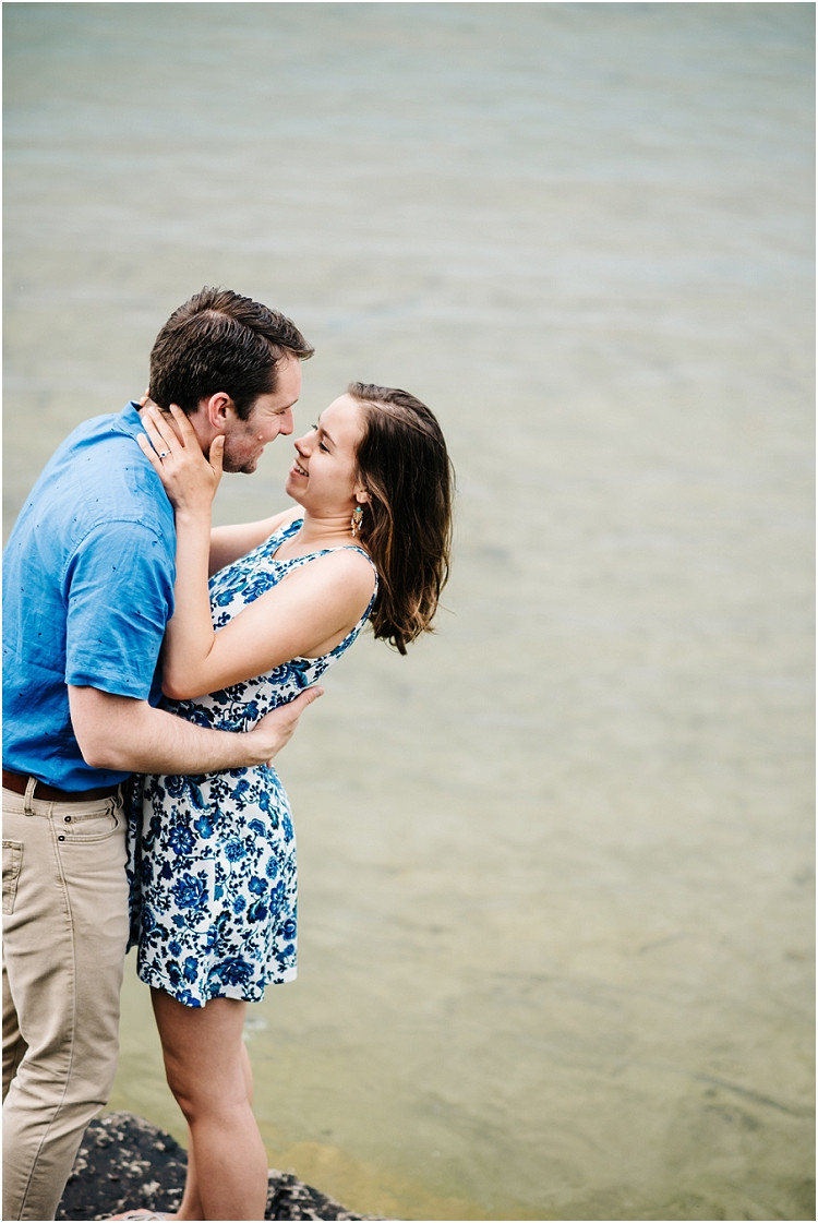 engaged-couple-holding-close-by-lake-at-cave-point-engagement-session-by-milwaukee-wedding-photographer-kyra-rane-photography