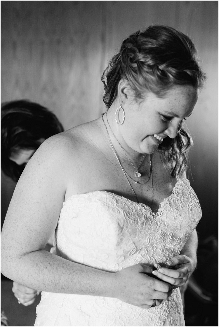 bride-smiling-while-getting-wedding-dress-buttoned-at-minnesota-wedding-by-green-bay-wedding-photographer-kyra-rane-photography