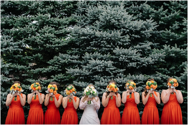 bride-and-bridesmaids-behind-floral-bouquets-at-pamperin-park-wedding-by-appleton-wedding-photographer-kyra-rane-photography