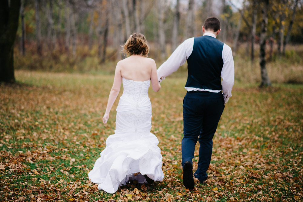 bride-and-groom-walking-on-fall-day-at-wedding-party-gifts-that-give-back-by-appleton-wedding-photographer-kyra-rane-photography