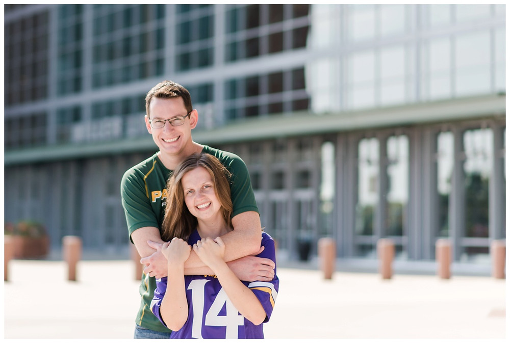 engaged-couple-arms-around-each-other-smiling-at-camera-at-downtown-green-bay-engagement-session-by-green-bay-wedding-photographer-kyra-rane-photography