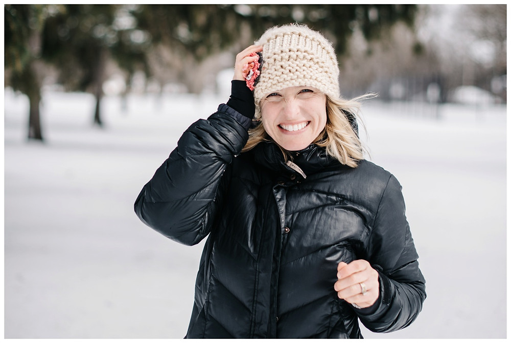 woman-holding-hat-at-winter-portrait-session-at-pierce-park-by-green-bay-wedding-photographer-kyra-rane-photography