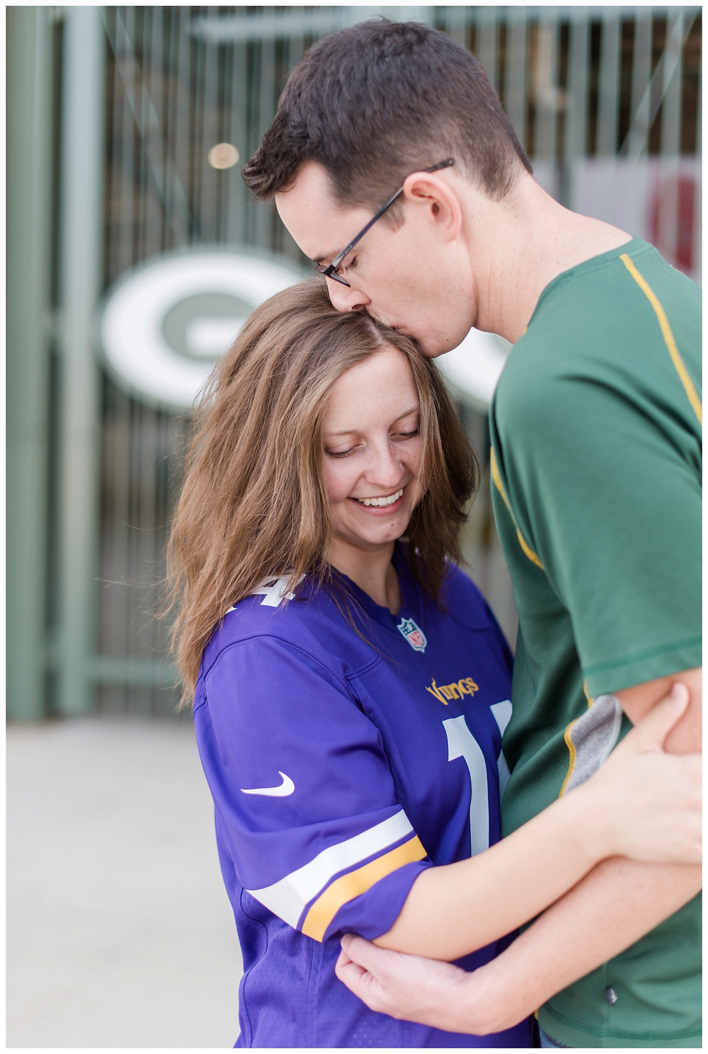 engaged-couple-kissing-forehead-holding-arms-at-downtown-green-bay-engagement-session-by-green-bay-wedding-photographer-kyra-rane-photography
