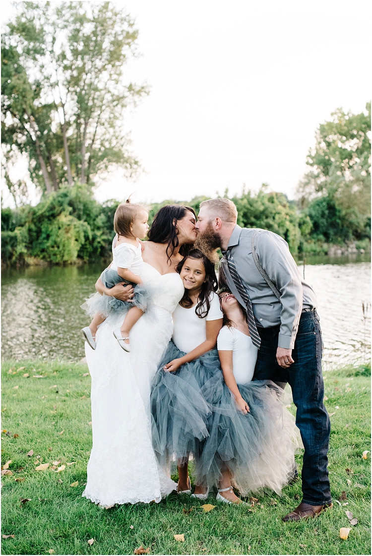 family-photo-mom-and-dad-kissing-at-little-chute-waterfront-wedding-by-appleton-wedding-photographer-kyra-rane-photography