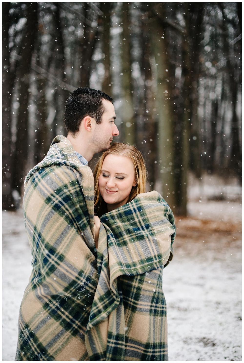 engaged-couple-snuggling-under-blanket-at-snowy-sheboygan-engagement-session-by-appleton-wedding-photographer-kyra-rane-photography