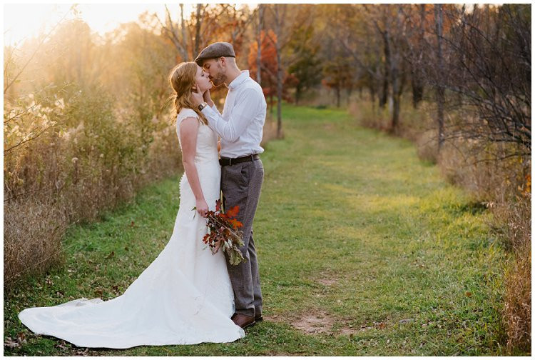 husband-and-wife-kissing-on-forest-trail-while-sun-sets-at-anniversary-session-at-high-cliff-state-park-by-appleton-wedding-photographer-kyra-rane-photography