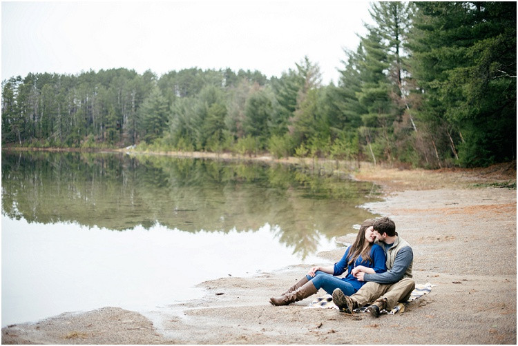 engaged-couple-about-to-kiss-sitting-by-lake-at-northwoods-lakeside-engagement-session-by-green-bay-wedding-photographer-kyra-rane-photography