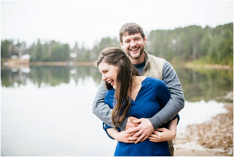 engaged-couple-being-held-laughing-by-lake-at-northwoods-lakeside-engagement-session-by-milwaukee-wedding-photographer-kyra-rane-photography