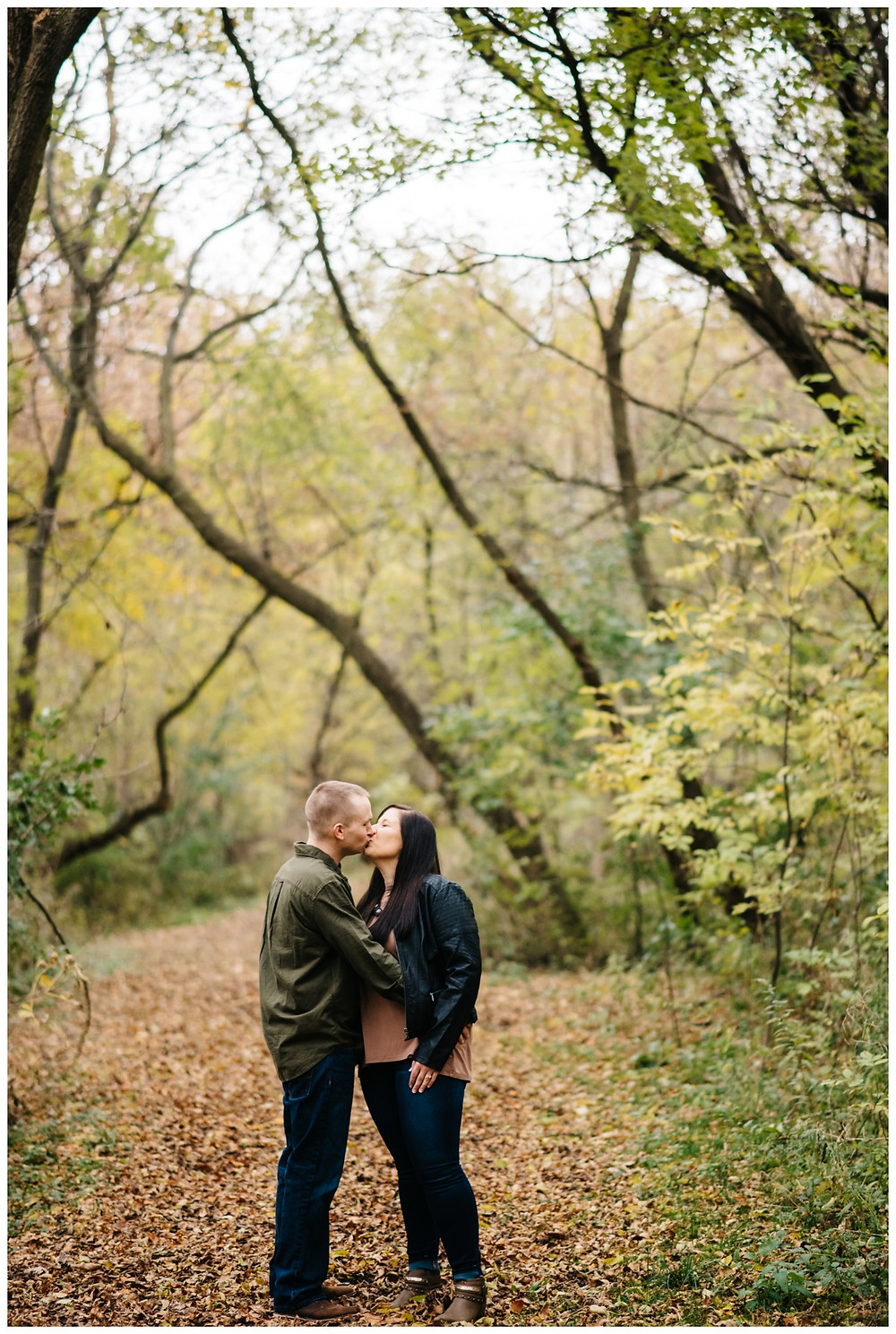 engaged-couple-kissing-in-woods-at-green-bay-engagement-session-by-green-bay-wedding-photographer-kyra-rane-photography