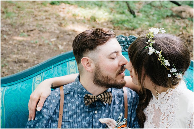 bride-and-groom-on-teal-couch-in-woods-at-july-4th-elopement-by-appleton-wedding-photographer-kyra-rane-photography
