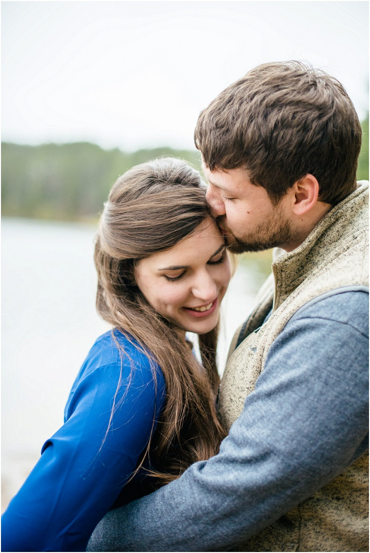 engaged-couple-kissing-forehead-at-northwoods-lakeside-engagement-session-by-green-bay-wedding-photographer-kyra-rane-photography