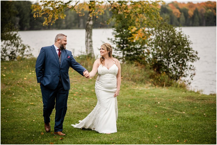bride-and-groom-holding-hands-walking-at-northern-wisconsin-autumn-wedding-by-green-bay-wedding-photographer-kyra-rane-photography