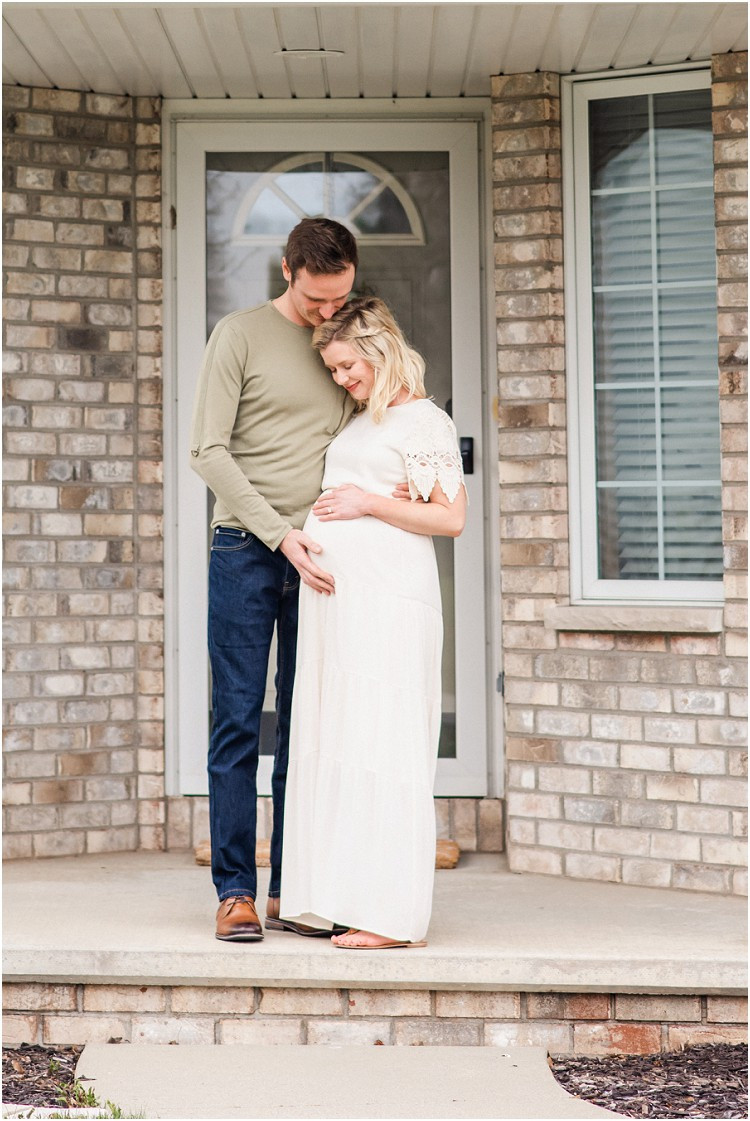 father-and-mother-to-be-smiling-at-baby-bump-front-steps-at-the-front-porch-series-by-appleton-wedding-photographer-kyra-rane-photography