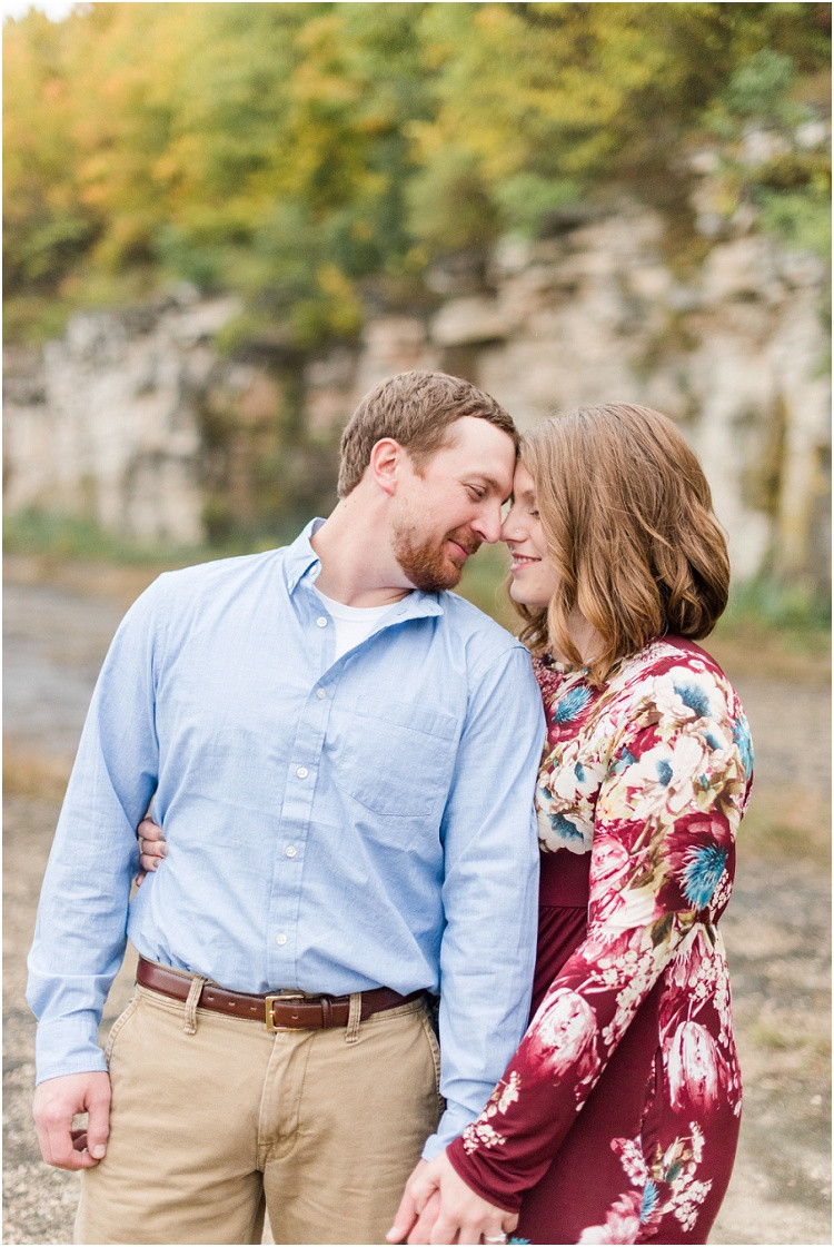 engaged-couple-snuggle-close-by-bluffs-at-high-cliff-engagement-session-by-milwaukee-wedding-photographer-kyra-rane-photography