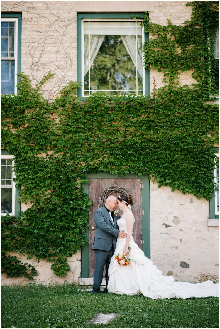 bride-and-groom-under-wall-ivy-at-wisconsin-farm-wedding-by-green-bay-wedding-photographer-kyra-rane-photography