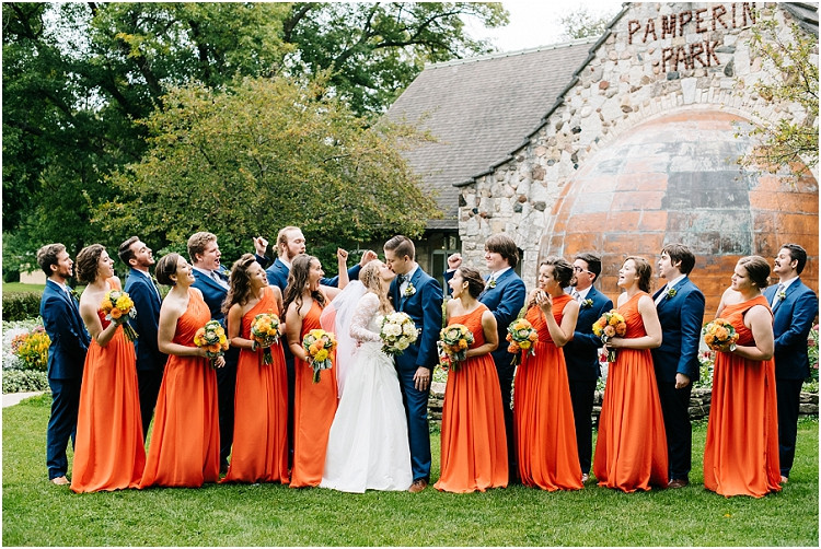 bride-and-groom-kissing-with-wedding-party-at-pamperin-park-wedding-by-green-bay-wedding-photographer-kyra-rane-photography
