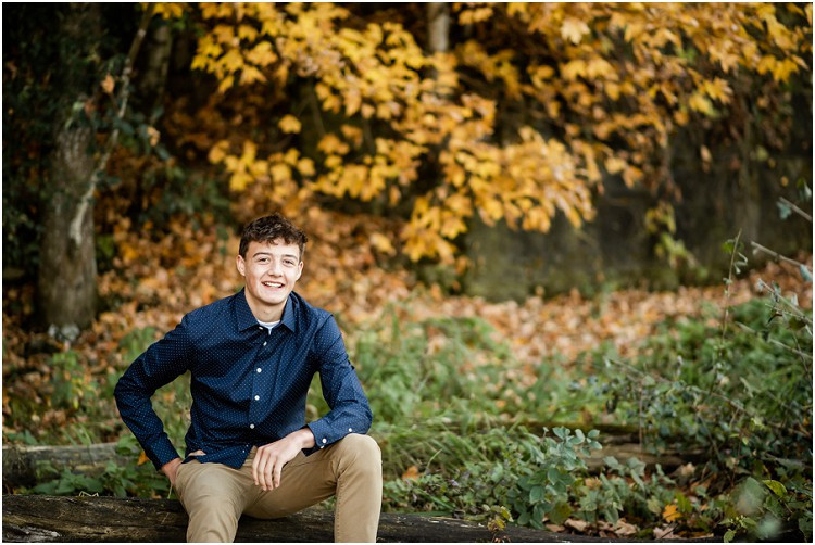 boy-sitting-on-log-smiling-at-camera-at-senior-session-at-high-cliff-state-park-by-appleton-wedding-photographer-kyra-rane-photography