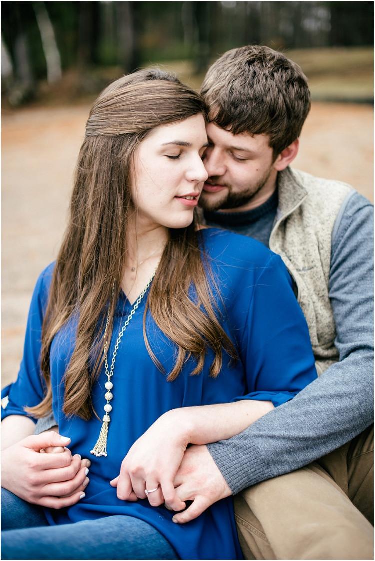 engaged-couple-snuggled-close-at-northwoods-lakeside-engagement-session-by-appleton-wedding-photographer-kyra-rane-photography