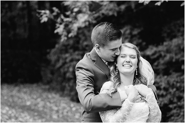 grooms-arms-wrapped-around-bride-at-pamperin-park-wedding-by-appleton-wedding-photographer-kyra-rane-photography