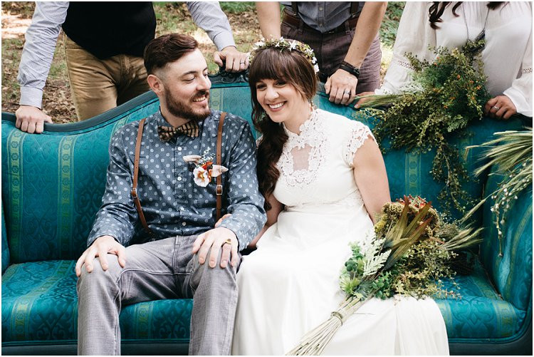 bride-and-groom-laughing-on-teal-couch-in-woods-with-wedding-party-at-july-4th-elopement-by-green-bay-wedding-photographer-kyra-rane-photography