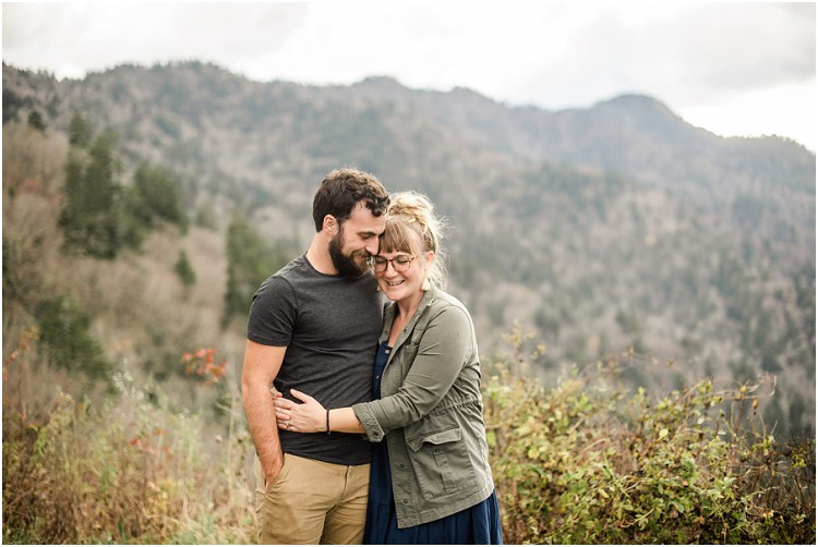 husband-and-wife-smiling-with-temples-together-and-wife-with-hands-wrapped-around-husband-at-family-session-in-the-great-smoky-mountains-by-green-bay-wedding-photographer-kyra-rane-photography