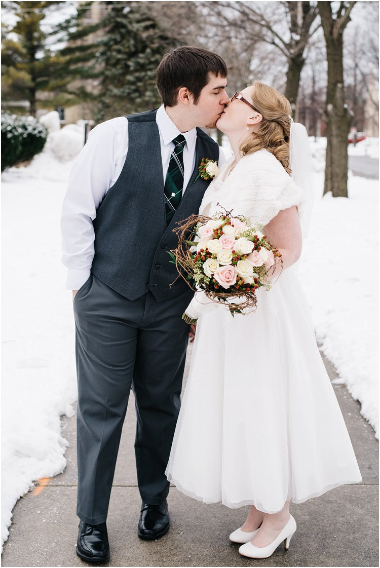 bride-and-groom-share-kiss-on-sidewalk-at-sheboygan-winter-wedding-by-green-bay-wedding-photographer-kyra-rane-photography