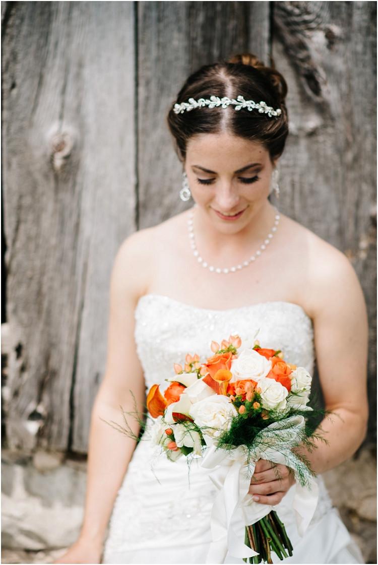 bride-holding-orange-floral-bouquet-at-wisconsin-farm-wedding-by-appleton-wedding-photographer-kyra-rane-photography