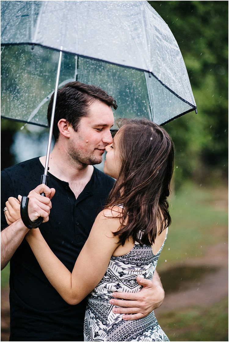 engaged-couple-about-to-kiss-under-umbrella-at-cave-point-engagement-session-by-green-bay-wedding-photographer-kyra-rane-photography