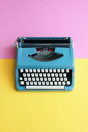 Vintage blue typewriter over a pastel ba