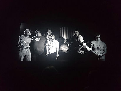 Black & White photgraph of Delta 7 Band on screen, from screening of the documentary short film We Rise by Rosie Baldwin