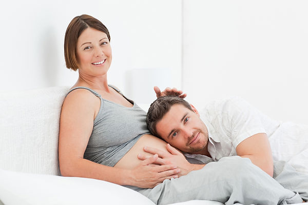 A young couple are laying in bed together. A pregnant women has her mate with his head against her pregnant belly and they are both smiling.