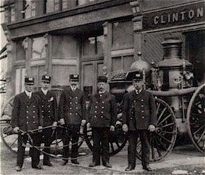 Members of the Steam Company stand next to the horse drawn steam pump