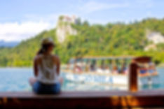 A girl sitting on a bank in Bled, Slovenia. Bled lake.