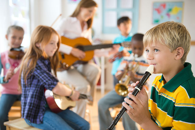 children playing a variety of instruments (recorder, violin, trumpet, ukulele, drum) with adult playing guitar