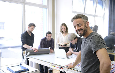 People at business desk man smiles at camera NSBA