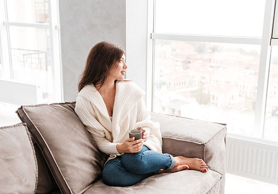 Woman on couch drinking coffee - covered by All Seasons Insurance