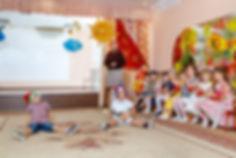 Фотографировали осенний утренник в детском саду. Дети играют и хлопают в ладоши.