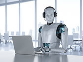 robot wearing a headset at a laptop