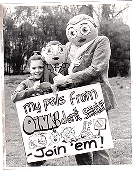 "'Sarah Gregory', Little Frank and Big Frank hold a sign saying ""My pals from Oink! don't smoke - Join 'em!"""