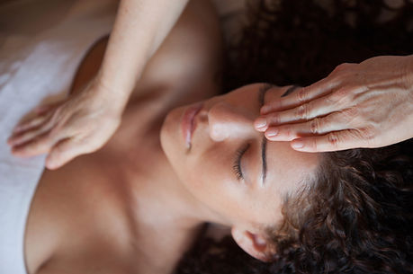 Image of a woman receiving a reiki treatment with healers hands on her forehead and above her heart