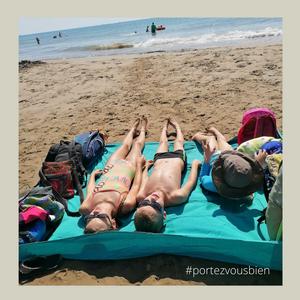 se reposer, bronzer, en famille sur un drap housse ou une nappe étalé sur la plage, à l'abri du vent et du sable qui vole.
