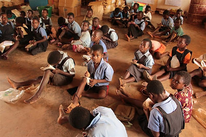 Malawian children learn on the floor.