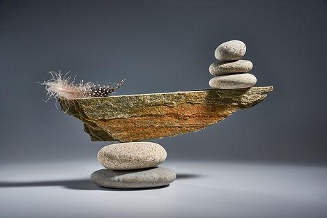Balancing pyramid of sea pebbles on a gr