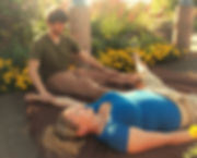 A Thai massage therapist works on a young woman in a garden with yellow flowers and sunshine