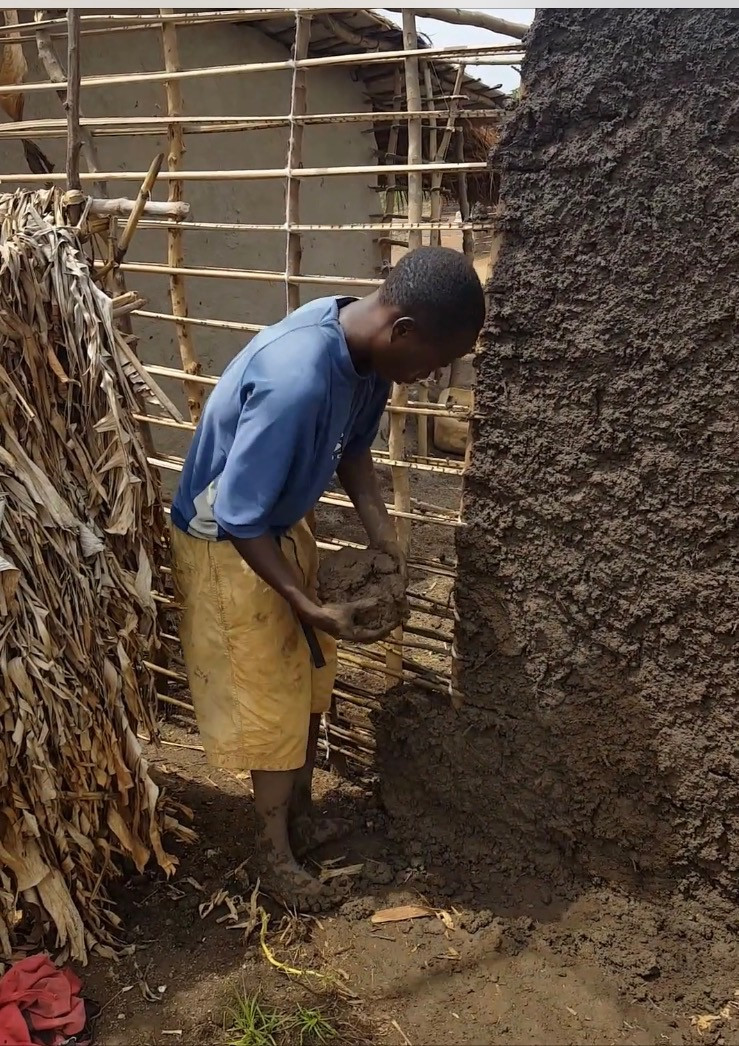 A young refugee in Nakivale building his own house out of mud and sticks.