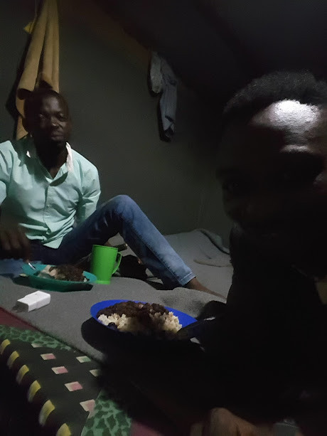 Sedrick and his friend having dinner in Rwamwanja.